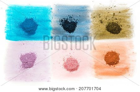 six samples of bright dry pigment in grinded and poured form.
