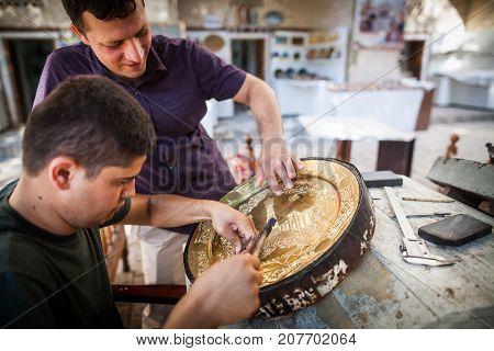 Bukhara Uzbekistan - June 4 2017: Artisans carve into metal plates in the historical city of Bukhara Uzbekistan.