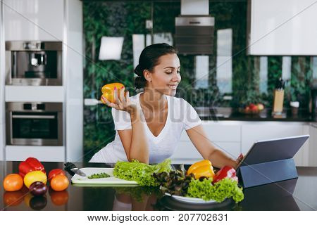 Young Woman Looking At Recipe In Laptop In Kitchen. Healthy Food - Vegetable Salad. Diet. Dieting Co