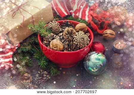 Christmas decoration - red bowl full of fir-cones gift box wrapped in kraft paper pine branches candle nuts anise apples christmas toys and red and white striped winter scarf. Christmas theme. Dark wooden background.