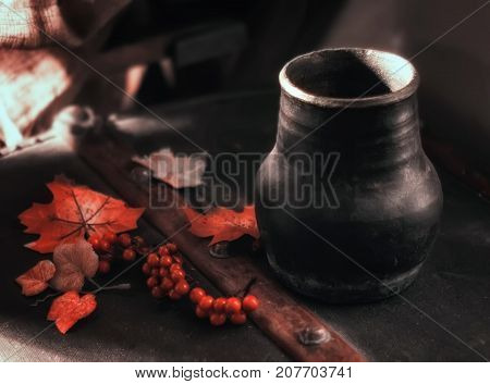 Autumn dark still life with a jug orange leaves and rowan berries. Selective focus soft blur filter.