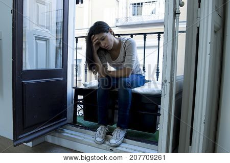 young sad and desperate Latin woman sitting at home balcony looking destroyed and depressed suffering depression feeling lonely unhappy and hopeless in mental health and crisis concept