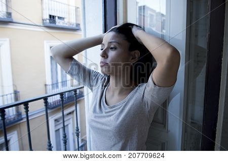 young sad and desperate Latin woman at home balcony looking destroyed and depressed suffering depression feeling lonely unhappy and hopeless in mental health and crisis concept
