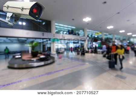 CCTV security indoor camera system operating with blurred image of passenger walking in airport terminal people transportation surveillance security and safety technology concept