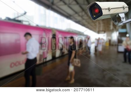 CCTV security indoor camera system operating with people waiting for sky train at train station people transportation surveillance security and safety technology concept
