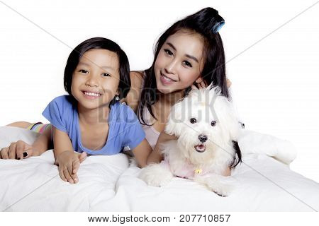 Image of pretty mother and her daughter playing with their Maltese dog on the bed isolated on white background