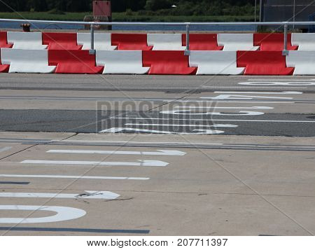 Car Lanes at Ferry Boarding with Red and White Striped Crash Barriers