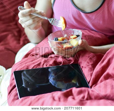 Man Eating Fruit And Using Tablet Computer