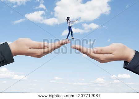 Blind businesswoman finding a way while walking on two helping hands at the sky