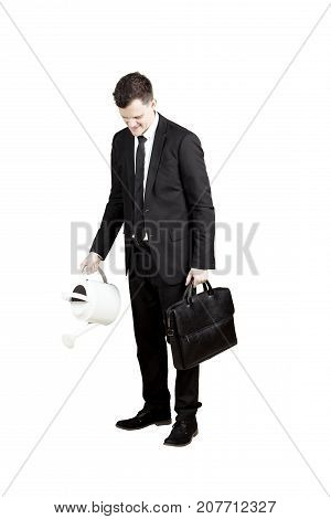 Caucasian businessperson pouring water from watering can while holding a briefcase isolated on white background