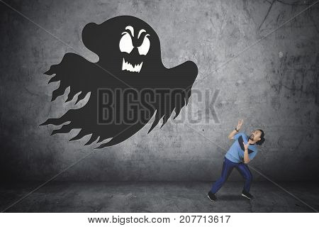Picture of young African man looks scared while running away from a ghost