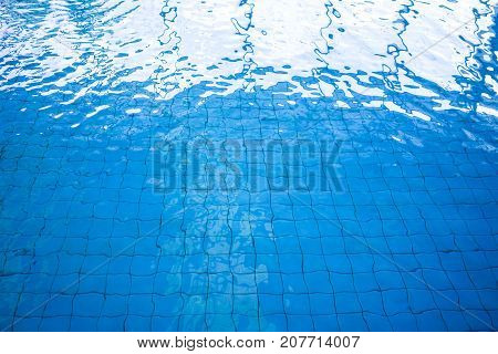 Blue and bright ripple water and surface in swimming pool. Beautiful motion wave in pool with square pattern floor