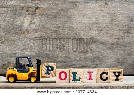 Yellow plastic forklift hold letter P to complete word policy on wood background