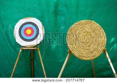 Two different archery target rings during an archery competition. Green background.
