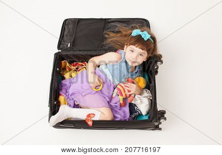 Girl Lying In The Suitcase With Things On A White Background