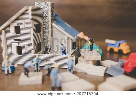 Miniature People Worker Repairing Are Repairing House On Wooden Background.