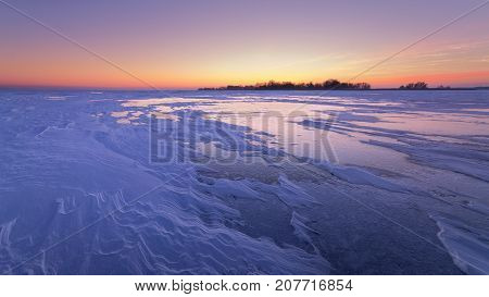 purple dawn clear sky / patterns of snow on a frozen lake