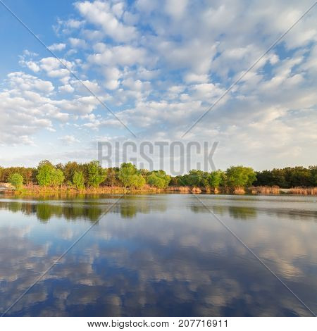 autumn lake fluffy clouds / calm water landscape clouds reflected in the water