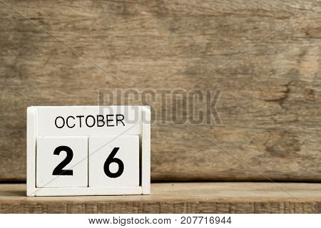 White block calendar present date 26 and month October on wood background