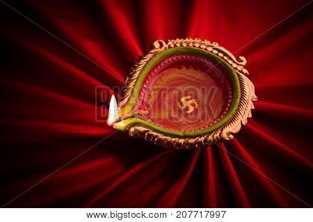 Big illuminated diwali diya or clay lamp placed over satin cloth creating rays effect in cloth, moody lighting, selective focus
