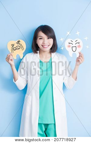 woman dentist take decay and health tooth board on the blue background