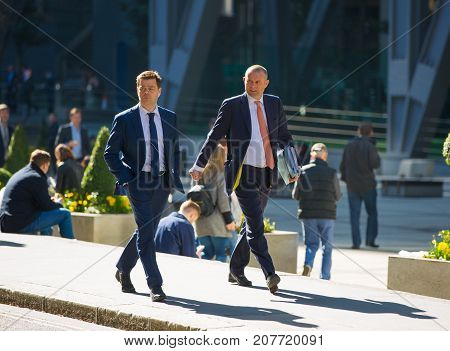 London, UK - March 15, 2017: City of London. Business people in suits walking on the street. Modern busy business life concept.