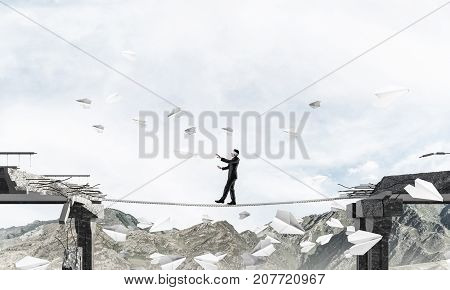 Businessman walking blindfolded on rope among flying paper planes and above huge gap in bridge as symbol of hidden threats and risks. Nature view on background. 3D rendering.