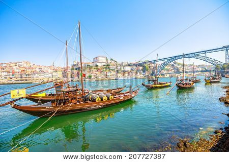 Porto, Portugal - August 13, 2017: Picturesque Oporto waterfront. A traditional rabelo boat on Douro River with Dom Luis I Bridge and Ribeira skyline from Vila Nova de Gaia. Sunny day.