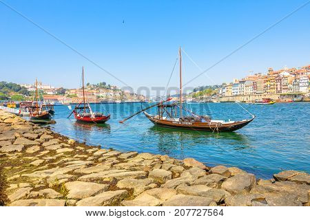 Porto, Portugal - August 13, 2017: Oporto waterfront with Ribeira skyline.A traditional Rabelo boat, used for transportation of port wine from Douro Valley region, to wine cellars in Vila Nova de Gaia