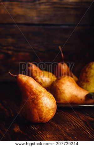 Golden Pear on Wooden Table and Few Pears on Backdrop. Vertical Orientation.