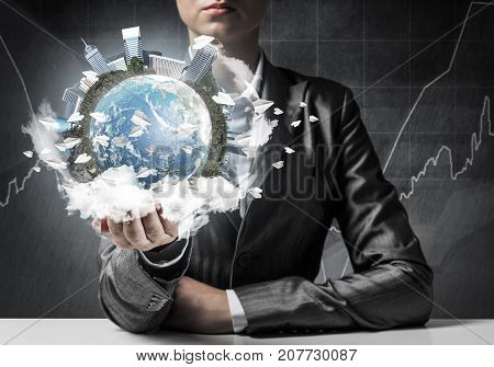 Closeup of businessman in suit keeping in hands Earth globe with buildings and flying paper planes. Elements of this image are furnished by NASA.