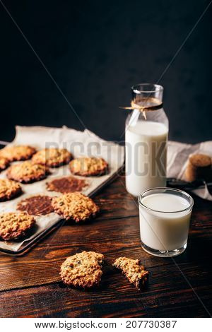 Oatmeal Cookies with Raisins and Glass of Milk for Breakfast. Some Cookies on Parchment Paper with Bottle on Backdrop. Copy Space on the Top.