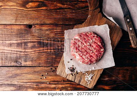 Raw Beef Patty with Spices on Cutting Board for Burger. View from Above.