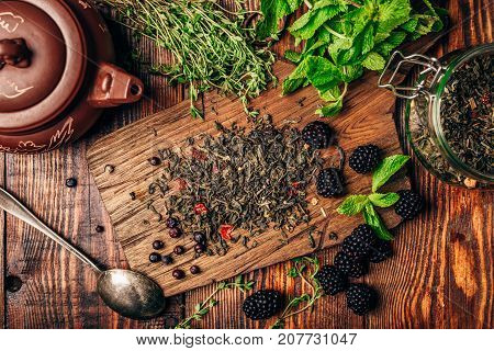 Heap of Dry Green Tea and Fresh Blackberries on Wooden Cutting Board. Bundles of Mint and Thyme Leaves. Clay Teapot. View from Above.