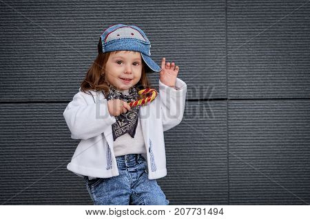 model child hip-hop.Children's fashion wear jeans posing against grey wall, minimalist street style children's clothing.the girl in the baseball cap, in the hands holding a Lollipop.