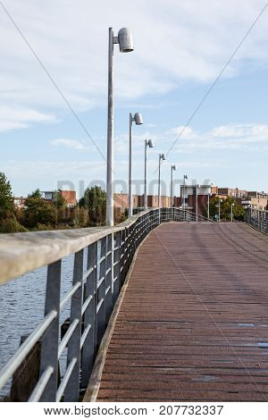 an wooden foot and bicycle bridge with street lighting
