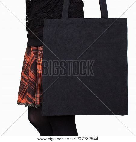 Mock-up. Girl in orange skirt holds black cotton tote bag. Handmade eco shopping bag for girls. Halloween mockups.