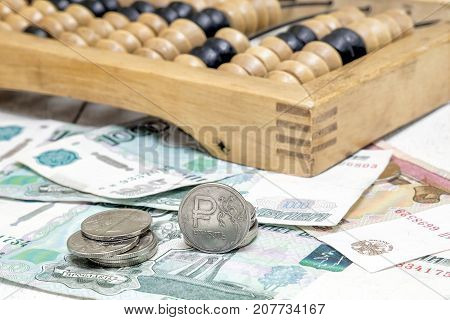 Iron ruble paper bills and old abacus. Business still life