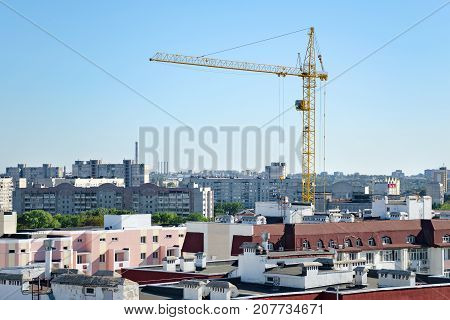 Building Crane Rises Above The Roofs Of Multi-storey Buildings. View Of The City.