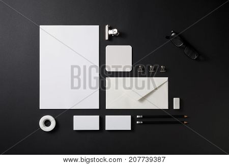 Blank stationery set on black paper background. Paperwork template. Responsive design mockup. ID template. Top view.