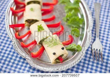 Funny food idea: caterpillar made from savory crepes with red pepper.