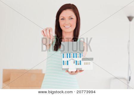 Gut aussehende Rothaarige Frauen halten ein Miniatur-Haus stehen auf dem Boden zu Hause