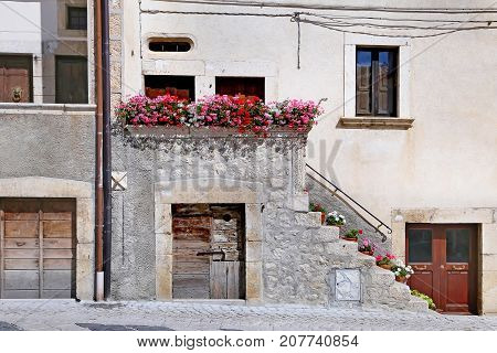 PESCOCOSTANZO ITALY - AUGUST 21 2015: Nice facades in steep alley. The mountain village - about 1400 m above sea - Pescocostanzo in the region of Abruzzo Italy