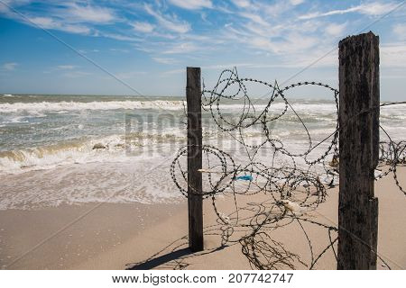 wire and blue sky with clouds. Safety fence of barbed wire against the blue sky and sea