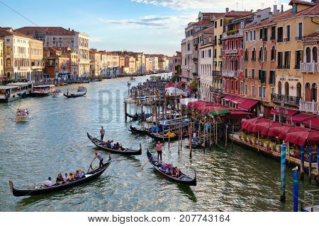 VENICE,ITALY - JULY 25,2017 : The Grand Canal in Venice at sunset with gondolas and old colorful buildings