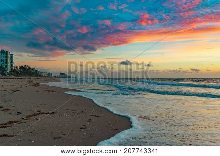 colorful clouds in the sky over the sand waves and buildings on the beach on a windy morning