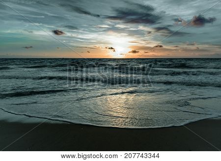 pastel colors over the ocean as the tides turn and the sun rises on a windy morning at the beach
