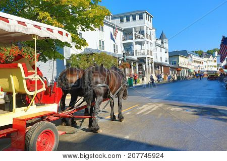 MACKINAC ISLAND, MICHIGAN - SEPTEMBER 12, 2017:  Horse drawn carriages and bikes are the popular modes of transportation in Mackinac Island, Michigan.