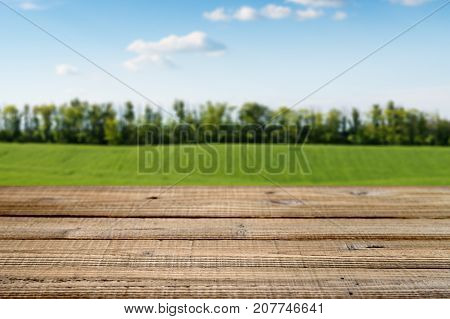 Old wooden table with green field background. Shallow depth of field.