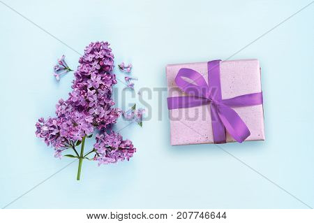 Lilac flowers and gift box on blue background